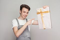 Cheerful modern teenager in demin overalls and white t-shirt sta. Nding and pointing finger to present with yellow bow and toothy smile, looking at camera stock photos