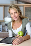 Cheerful modern woman with green apple Royalty Free Stock Photography