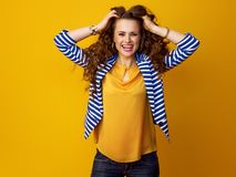 Cheerful modern woman in striped jacket on yellow background Royalty Free Stock Images