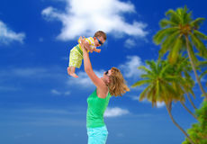 Cheerful mom with baby on the beach Royalty Free Stock Photography