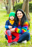 Cheerful mom and boy sitting on grass Royalty Free Stock Images