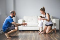 Cheerful mom and dad help their son to walk at home Royalty Free Stock Photos