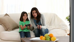 Cheerful mom encouraging her daughter to play video games Royalty Free Stock Photos