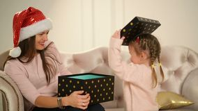 Cheerful Mom And Her Cute Daughter Baby Open A Gift. Parent And Little Child Having Fun Near Christmas Tree Indoors stock footage