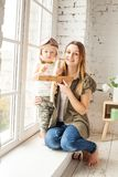 Cheerful Mom and her Son are Playing Wooden Handmade Plane Toys. Happy Loving Family Royalty Free Stock Photos