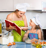 Cheerful mom showing girl recipe of omelette Stock Image