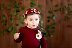 A cheerful 8-12 month old girl in a beautiful outfit smiles on a dark wooden background