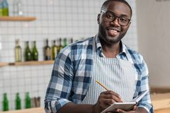 Smiling positive waiter standing with a notebook and writing. Cheerful mood. Pleasant young handsome waiter having a productive day at work while standing and Royalty Free Stock Photography