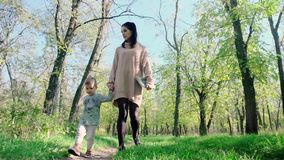 Cheerful mother with baby boy playing in autumn park. Beautiful woman holding her infant son outdoors stock footage