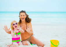 Cheerful mother and baby girl playing with sand Royalty Free Stock Photography