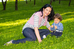 Cheerful mother and boy sit in grass Stock Photography