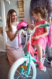 Cheerful mother buying new bicycle and helmet for girl in bike shop. Cheerful mother buying new bicycle and helmet for cute girl in bike shop stock photo