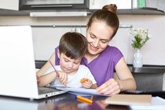 Cheerful mother cares of her son, being on maternity leave, works freelance with laptop computer, pose together at kitchen. Busy m. Om plays wit small boy, has Royalty Free Stock Photography