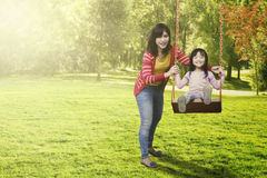 Cheerful mother and child playing swing Royalty Free Stock Images