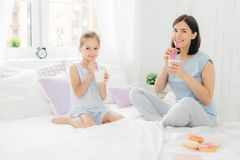 Cheerful mother and daughter dressed in pyjamas, have breakfast in morning, drink milk shake with doughnuts, sit crossed legs on c royalty free stock photography