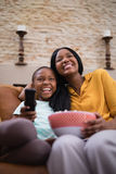 Cheerful mother and daughter enjoying television at home Stock Image