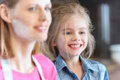 Cheerful mother and daughter in flour in kitchen Stock Photo