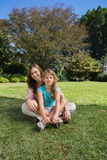 Cheerful mother and daughter on the grass. In the park smiling at camera Stock Photography