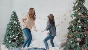 Cheerful mother and daughter having dance party on bed in luxury house.