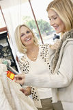 Cheerful mother and daughter looking at price tag of wedding gown in bridal store Stock Photography