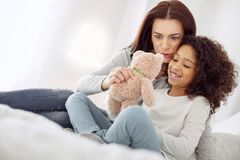 Cheerful mother and daughter looking at the toy. Having fun together. Attractive inspired dark-haired mother smiling and holding her daughters favourite toy Royalty Free Stock Image