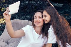 Cheerful mother and daughter making selfie photo by tablet PC Stock Photos