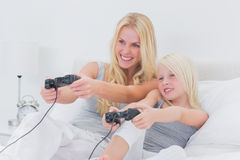 Cheerful mother and daughter playing video games. In bed Stock Images