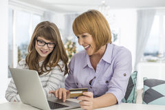 Cheerful mother and daughter shopping online at home during Christmas Stock Image