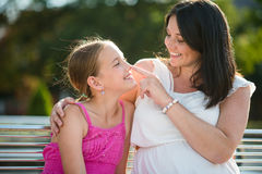 Cheerful mother and daughter sitting on park bench Stock Image