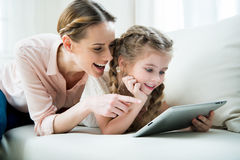 Cheerful mother and daughter using tablet at home Royalty Free Stock Images