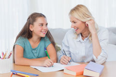 Cheerful mother and daughter writing together Royalty Free Stock Images