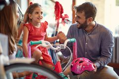 Cheerful mother and father buying new bicycle for little girl in bike shop stock photo