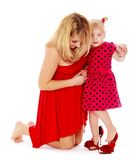 Cheerful mother helping her little daughter. To wear shoes .  on white Stock Photography