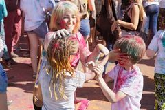 Cheerful mother and her children smear dry paint on each other`s body and clothes stock image