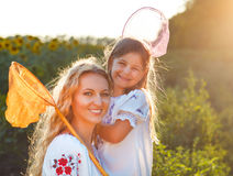 Cheerful mother and her daughter playing in a field with insect Stock Photos