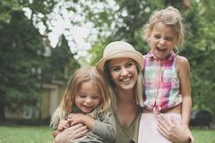 Cheerful mother with her daughters outdoor. Cheerful mother with her daughters in park. Young mother hugging her daughters Stock Image
