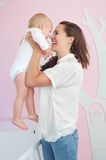 Cheerful mother hugging cute baby at home. Portrait of a cheerful mother hugging cute baby at home Stock Photos