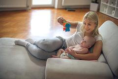 Cheerful mother playing with her baby boy at home. stock photography