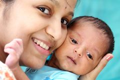 Cheerful mother playing with newborn royalty free stock images