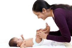 Cheerful mother playing with newborn royalty free stock photo