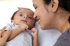 Cheerful mother playing with newborn royalty free stock photos