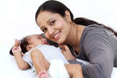 Cheerful mother playing with newborn royalty free stock image
