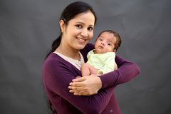 Cheerful mother playing with newborn stock photography