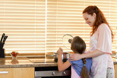 Cheerful mother showing her daughter how to cook Stock Photography