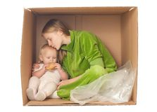 Cheerful mother sit in box with baby eating cookie Royalty Free Stock Photo