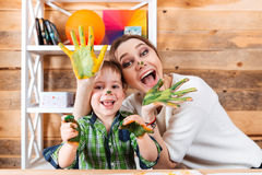 Cheerful mother and son with painted hands having fun together Royalty Free Stock Images