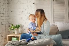 Cheerful Mother and Son Reading a Book at Home. Happy Loving Family. Woman and Child Boy Royalty Free Stock Photography