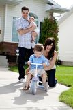 Cheerful Mother Teaching Son To Ride Tricycle. While husband holds daughter in background royalty free stock photo