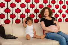 Cheerful mother and toddler son. Cheerful pregnant mom and toddler boy sitting on couch and having conversation Royalty Free Stock Photos