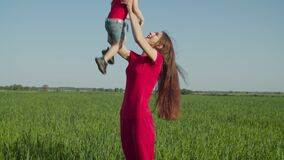 Cheerful mother tossing up child on wheat field